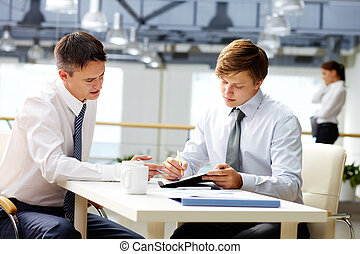 Business coaching - Senior businessman helping his younger...