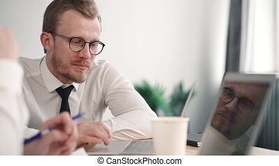 business colleague man helps office worker. entrepreneur explain coaching and pointing at laptop