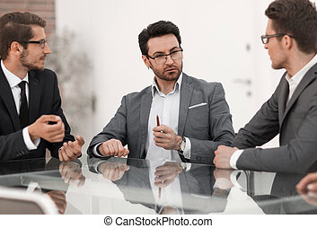 business colleagues are discussing something sitting at the office table