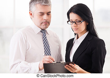 Business colleagues at work. Two concentrated business people discussing something while standing close to each other