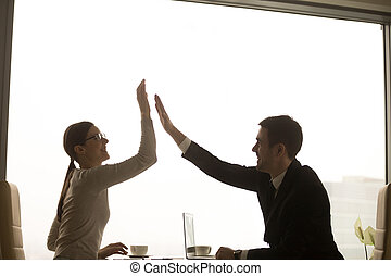 Happy smiling female and male business partners giving high five while sitting at desk in office. Businesswoman congratulating businessman with concluding good deal. Company employees enjoying success