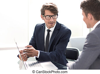 business colleagues discuss something sitting at their Desk