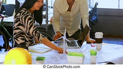 Business colleagues discussing over blueprint 4k - Business ...