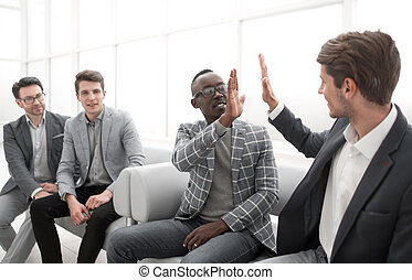 business colleagues giving each other a high five while sitting in the office lobby.