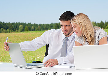 Business colleagues in sunny nature with laptop