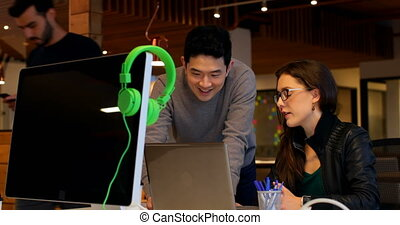 Business colleagues interacting with each other at desk in office 4k