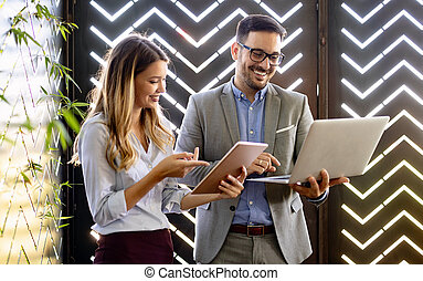 Business colleagues laughing and working while looking at the laptop