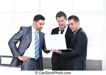 business colleagues looking at a laptop, standing in the lobby of the office.