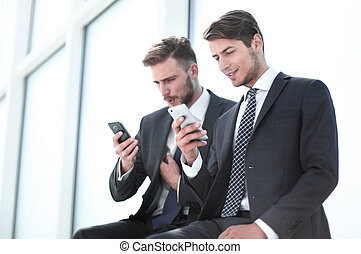 business colleagues read media files on their smartphones. ...