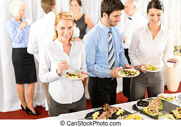 Business colleagues serve themselves at buffet catering ...