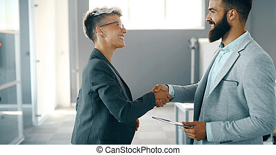 Business colleagues shaking hands after closing business deal