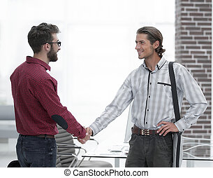 Business colleagues shaking hands at office