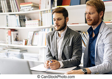 Business colleagues sitting at desk