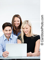 Business colleagues smiling while reading a laptop