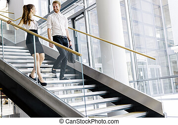 Business colleagues talking on stairs