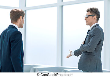 business colleagues talking standing in the office.