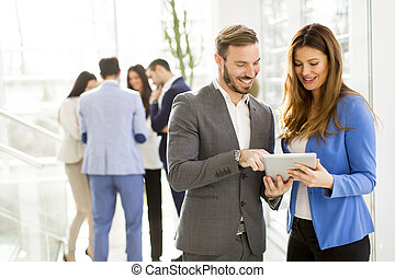Business colleagues using tablet  in modern office and discuss