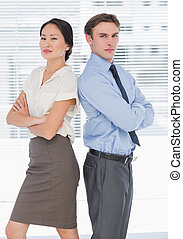 Business colleagues with arms crossed in office