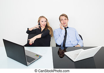 business colleagues with laptop and digital tablet in meeting at office desk. talking on the phone