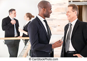 Business communication. Two cheerful business men talking to each other while their colleagues standing on background