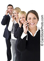 A team of one businessman and three businesswomen all talking on cell phones, the focus is on the brunette woman at the front.