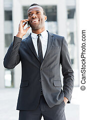 Business communications. Happy young African man in formalwear talking on the mobile phone and smiling while standing outdoors
