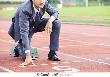Business competition - A businessman on a track ready to run...