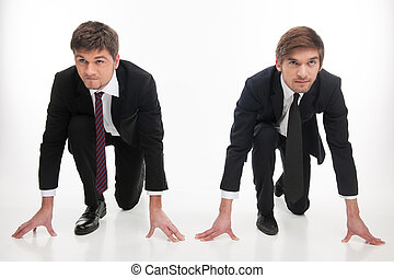 Business competition. Two angry young business people standing at the start line while isolated on white