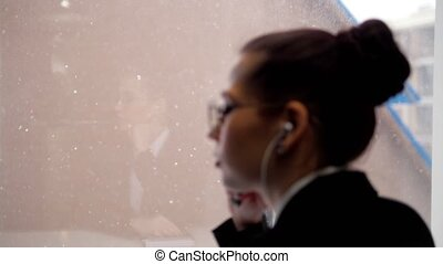 Business concept. A young woman in little headphones listening music standing by the window. Side view.