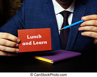 Business concept about Lunch and Learn with sign on blank business card.