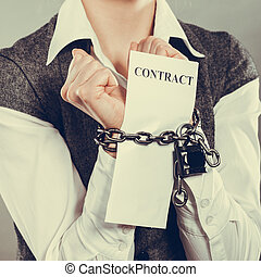 businesswoman with chained hands holding contract