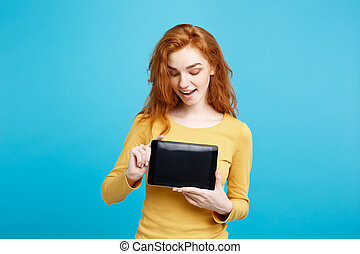 Business Concept - Close up Portrait young beautiful attractive redhair girl smiling showing digital tablet screen on black. Blue Pastel Background.