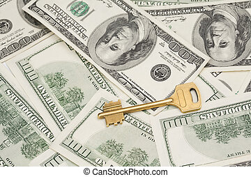 Business concept. Golden key on money background. Focus on key