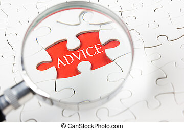 Business concept. Hand holding magnifying glass searching for a piece of jigsaw puzzle with ADVICE word.