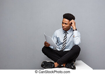 Business Concept - handsome young professional african american businessman serious reading paperworks.