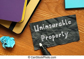 Business concept meaning Uninsurable Property with sign on the piece of paper.