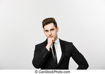 Business Concept: Portrait with copy space of handsome confident thoughtful man, holding hand on chin, standing over grey background and looking seriously to the side