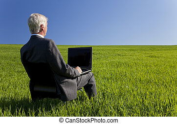 Business concept shot showing an older male executive using a laptop computer in a green field with a blue sky. Shot on location not in a studio.