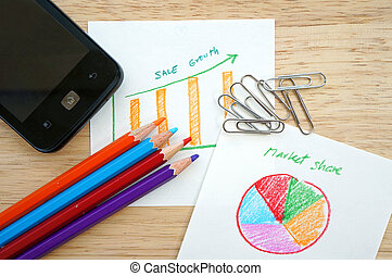 Business concept with pencil, paperclip, mobile phone and financial table and graph