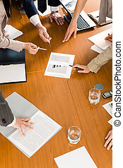 Business conference - Image of several hands pointing at...