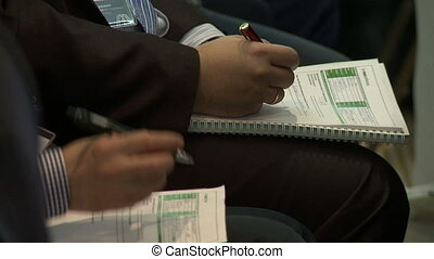 Business conference. Men make notes in manual