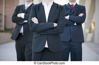 Business Confidence - three business people standing wearing...