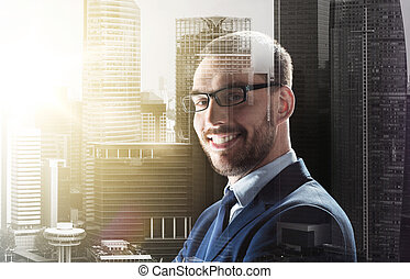 smiling businessman in glasses over city buildings