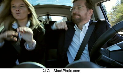 Business couple dancing in car