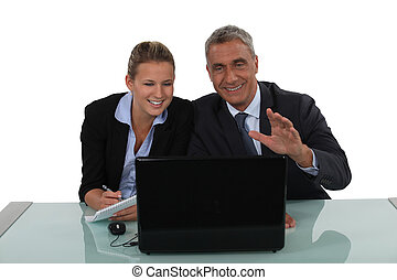 Business couple laughing at a laptop