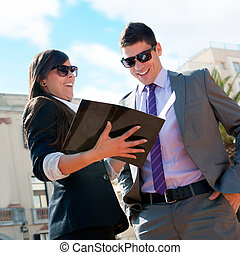 Business couple outdoors with catalog.