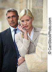 Business couple outside with a cellphone