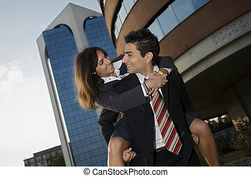business couple - businesswoman riding piggyback on his...