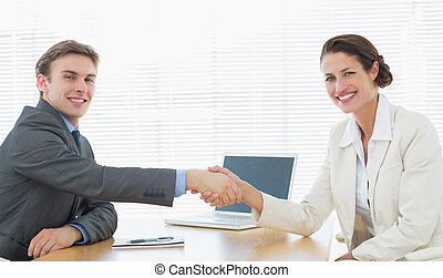 Business couple shaking hands in office