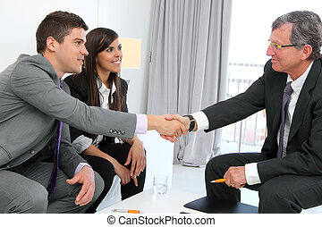 Business couple shaking hands with partner.